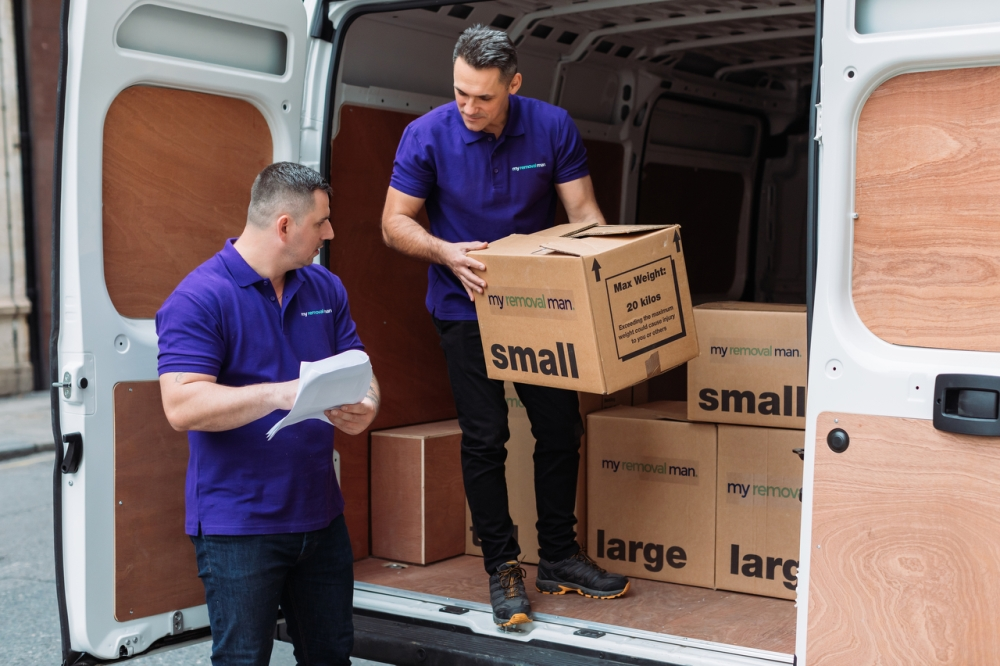 picture of two office movers staff loading boxes into van