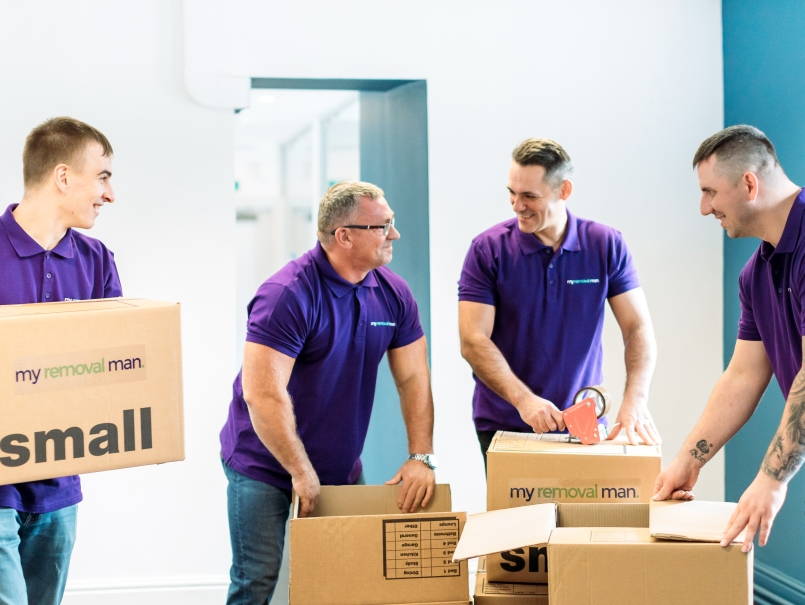 picture of four removal company men packing items into boxes for international removal
